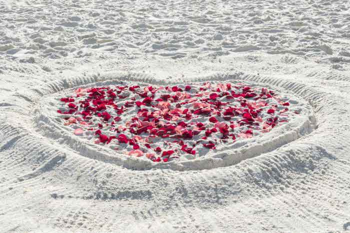 Heart drawn in sand with rose petals Rose Heart Wedding Package from Weddings Made Simple | Weddings Made Simple of Florida DISC Temperament Assessment, Pre and Post Marriage Coaching, Wedding Officiants and Wedding Ministers Naples Florida